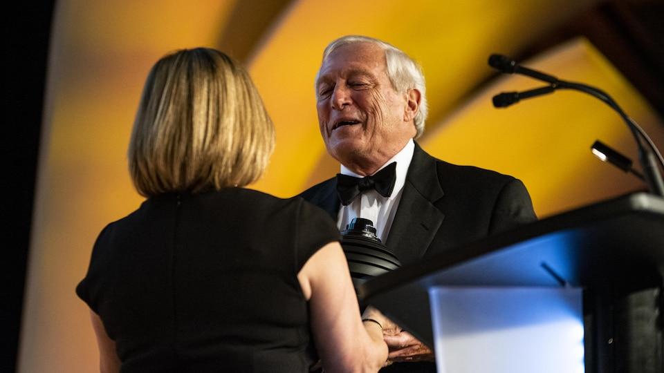 Une femme de dos remet un trophée à un homme en complet, souriant, sur une scène de gala.