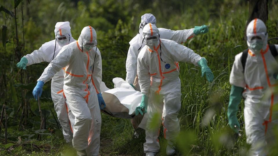 Des travailleurs funéraires en vêtements de protection portent les restes d'un homme mort d'Ebola.