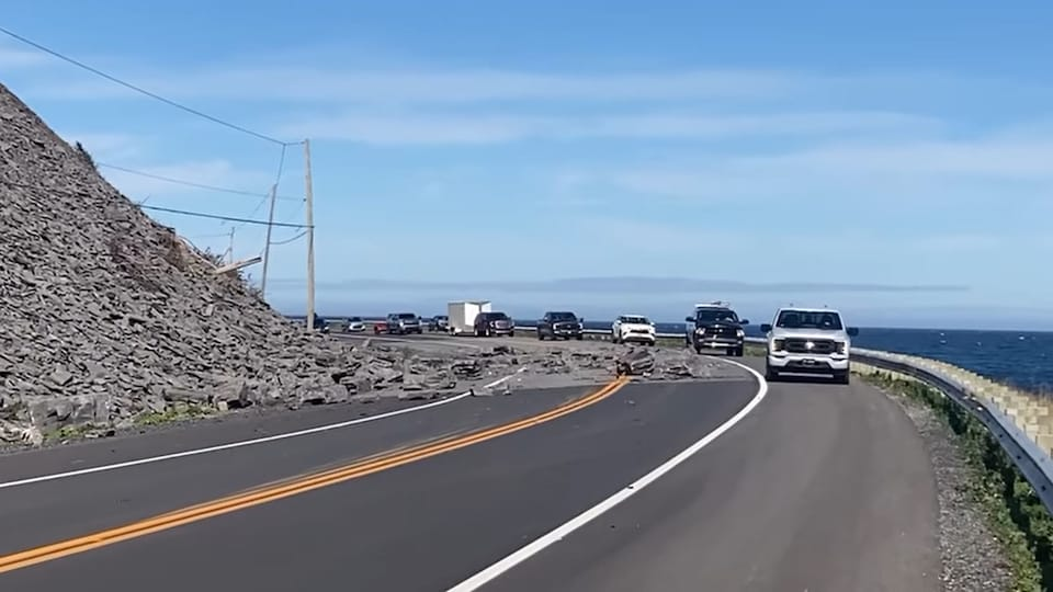Des voitures qui contournent des roches sur la route 132 bordée par la mer d'un côté et la montagne de l'autre.