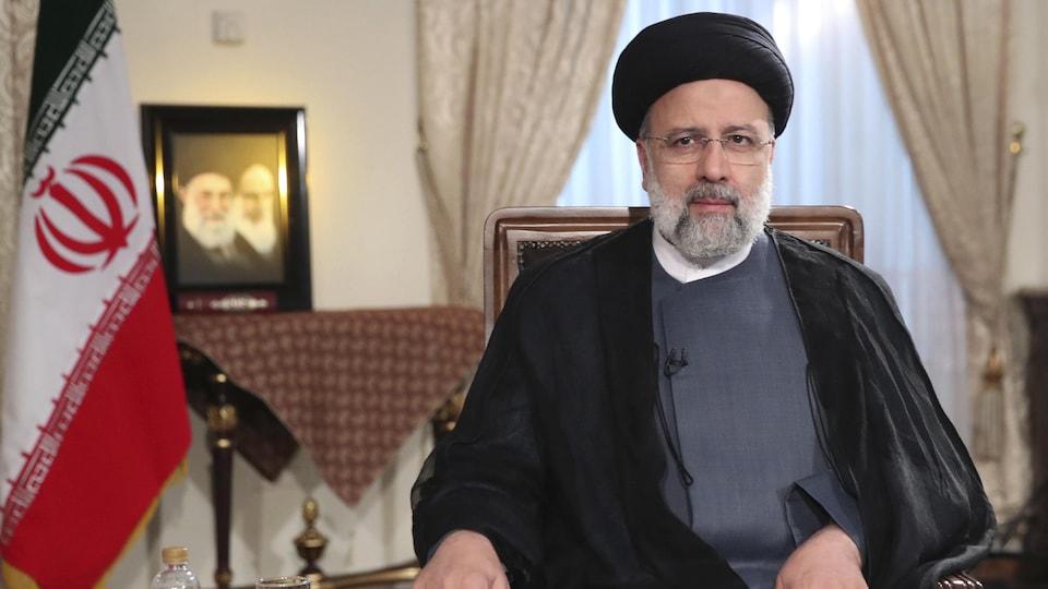 Ebrahim Raïssi est assis à côté d'un drapeau iranien.