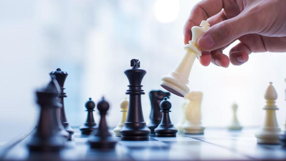 Une main bouge le roi dans un jeu d'échecs