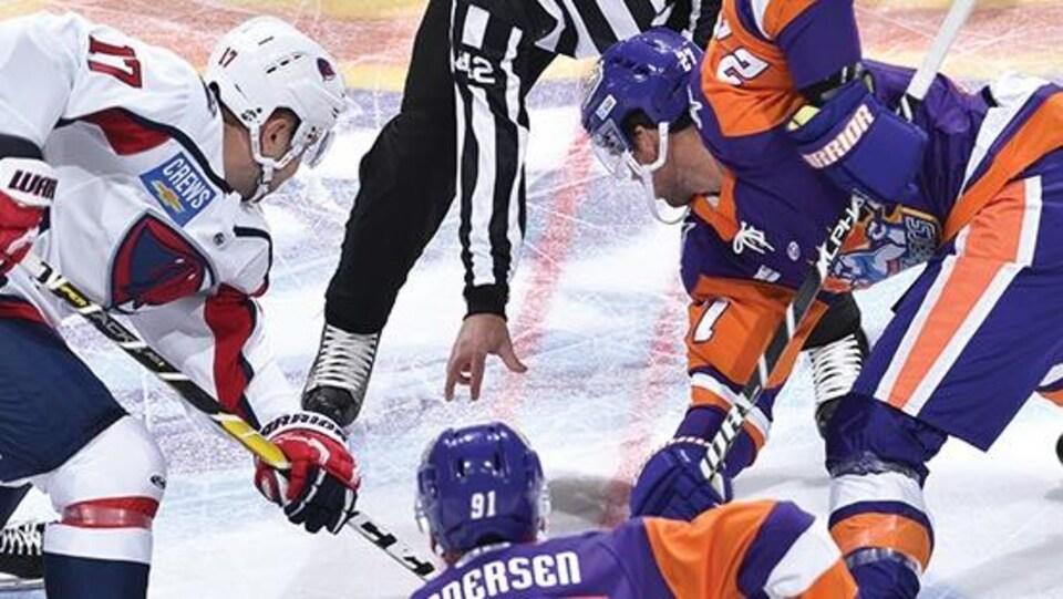 Des joueurs procèdent à une mise au jeu au hockey.