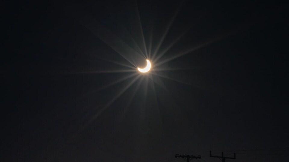Une éclipse annulaire partielle du Soleil au-dessus d'un pont.