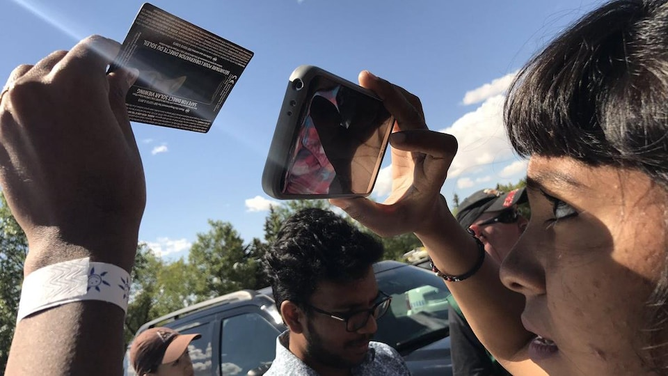 Une femme regarde l'éclipse solaire à travers son téléphine cellulaire.