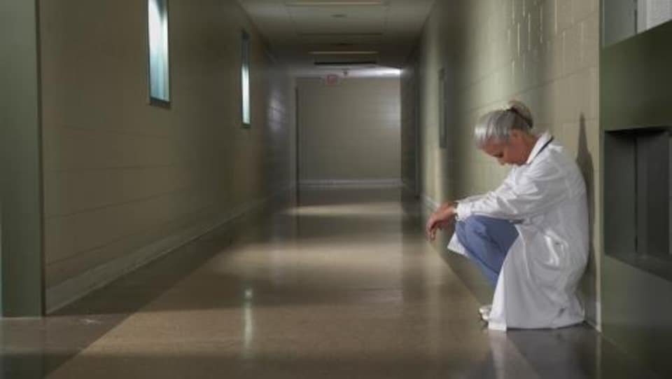 Une femme médecin est accroupie dans le corridor d'un hôpital.