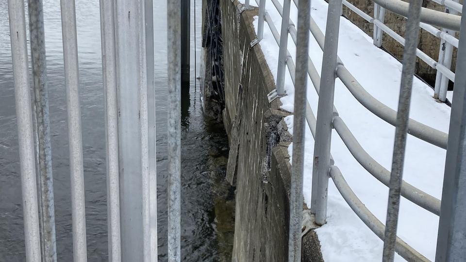 Vue de côté du mur de l'écluse endommagé.