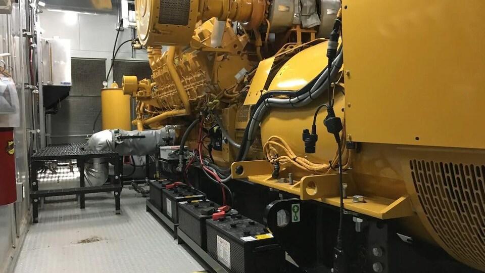 Une énorme génératrice reliée à des batteries et à des conduites de gaz.