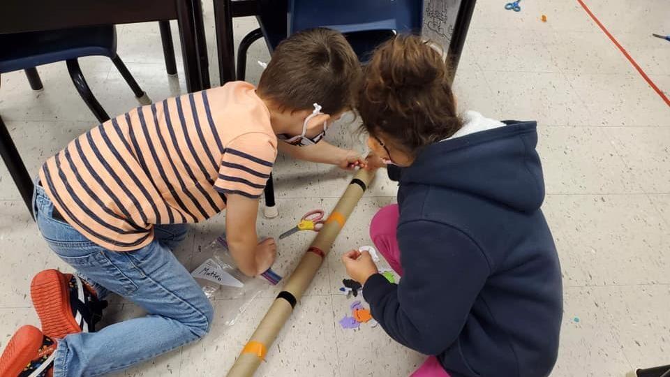 Des enfants en train de faire un bricolage avec un tube de carton.