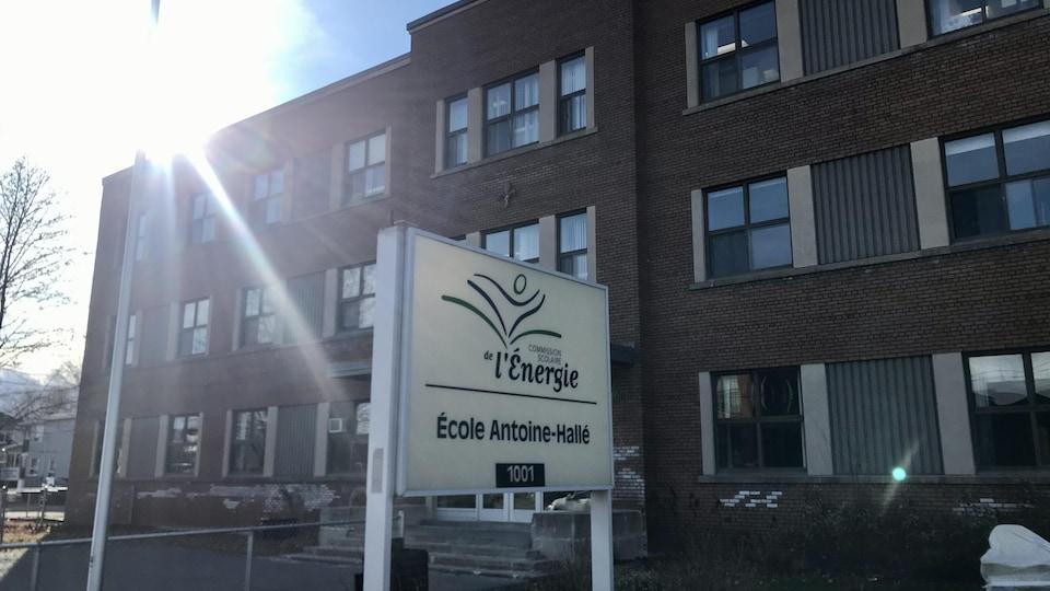 La pancarte avec le nom de l'école devant la façade extérieure de l'école.