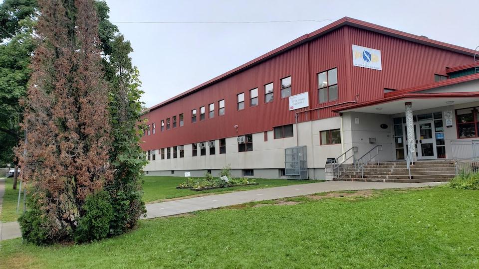 La façade l'École du Cap-Soleil, avec un revêtement rouge brique.