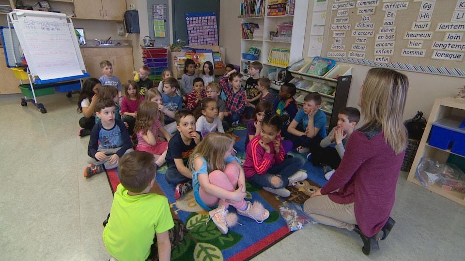Une quinzaine d'élèves assis à terre sur un tapis. Ils ont environ 5-6 ans. L'enseignante est à genoux devant eux, de dos à la caméra.