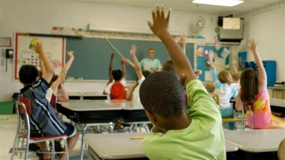 Des enfants assis sur leur chaise dans la classe lèvent la main.