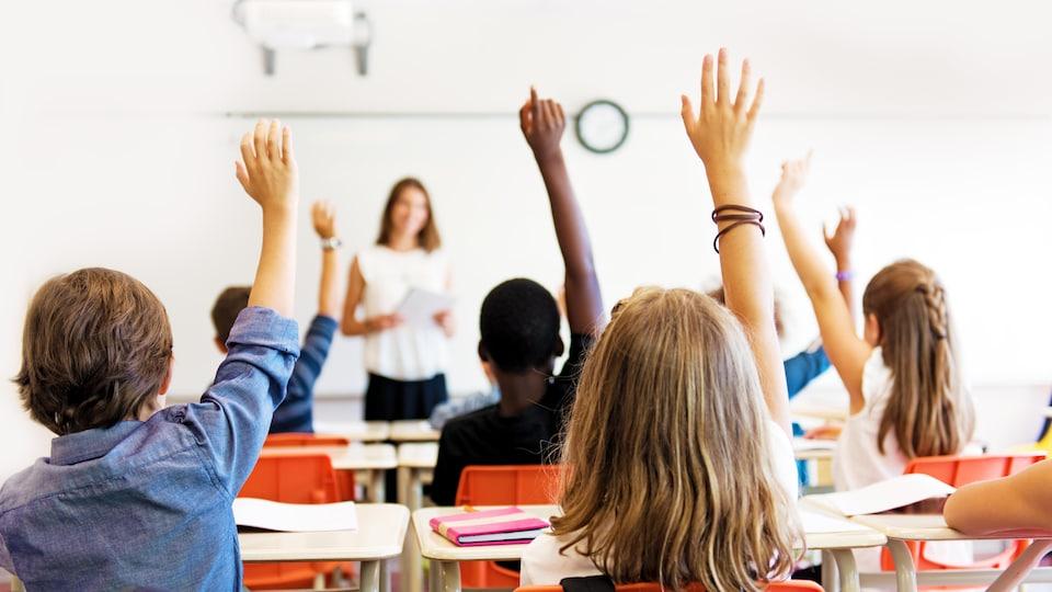 Des élèves assis en classe lèvent la main devant leur enseignante.