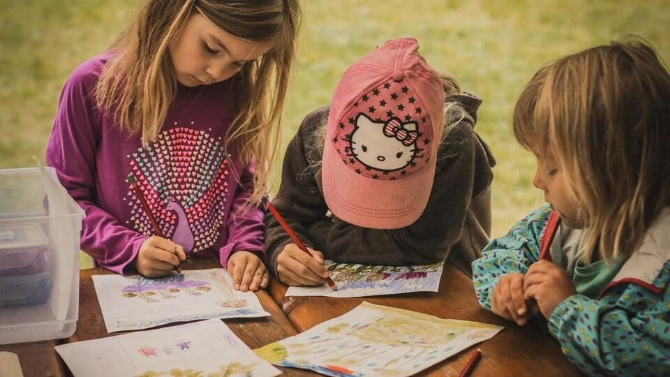 Trois fillettes à une table, à l'extérieur, en train de colorier des dessins qu'elles ont préalablement peints.