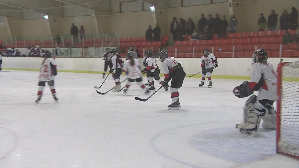 De jeunes hockeyeuses sur la patinoire devant le filet.