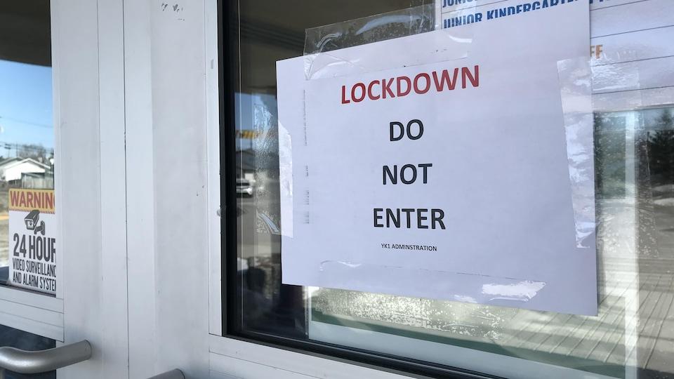 Une affiche à l'entrée de l'école demande de ne pas entrer.