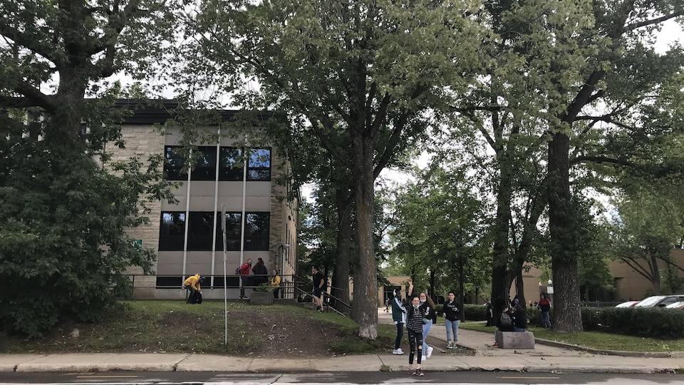 Un groupe d'élèves de l'autre côté d'une rue avec, en arrière-plan, une école