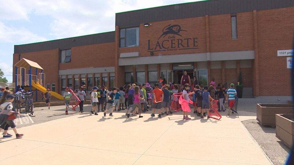 Des élèves se regroupent à une porte à la fin de la récréation.