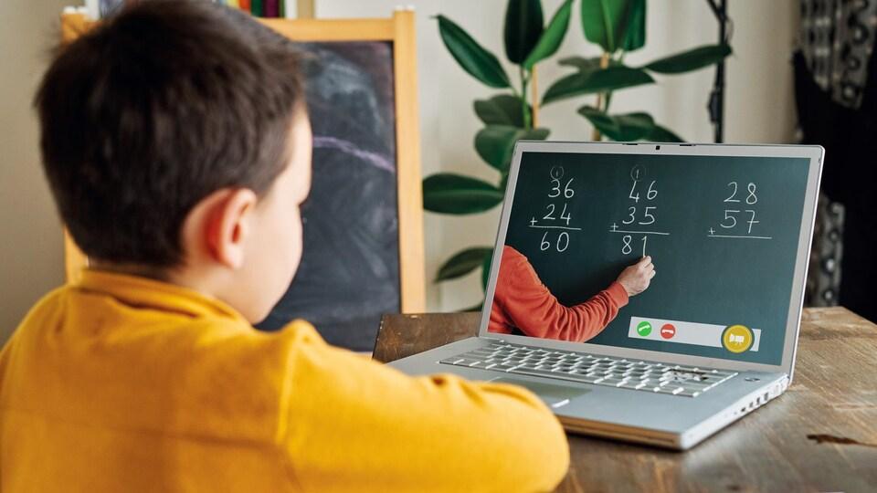 Un enfant devant un ordinateur portable suit un cours à distance.