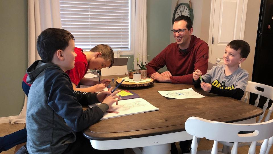 Mathéo, Loïc et Emanuel, avec leur père Jean-Marie, dessinent à la table.