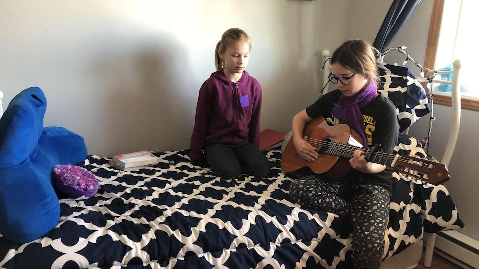 Deux jeunes filles sont assises sur un lit alors que l'une joue de la guitare.
