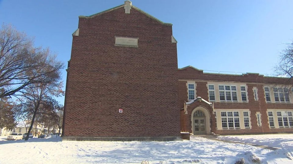 Façade de l'École Faraday, un bâtiment composé d'un mur de brique et d'une deuxième section avec des fenêtres.