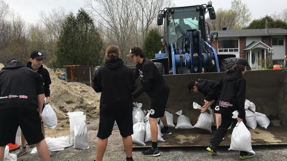 Des jeunes transportent des sacs de sable.