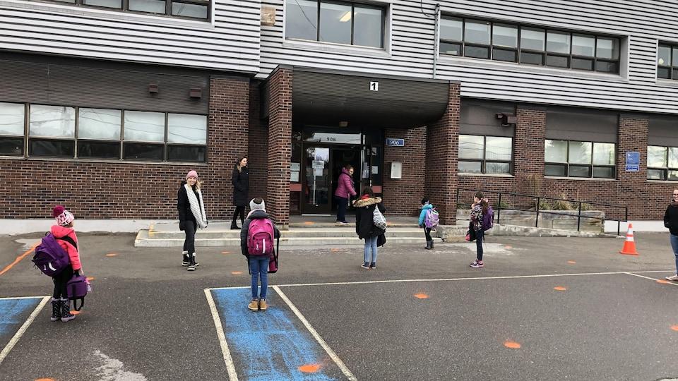 Des enfants loin les uns des autres attendent pour entrer dans l'école.