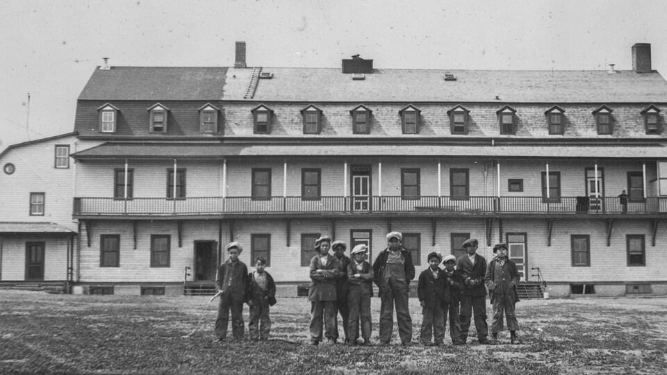 Des élèves garçons en habits de travail devant la bâtisse de l'école.