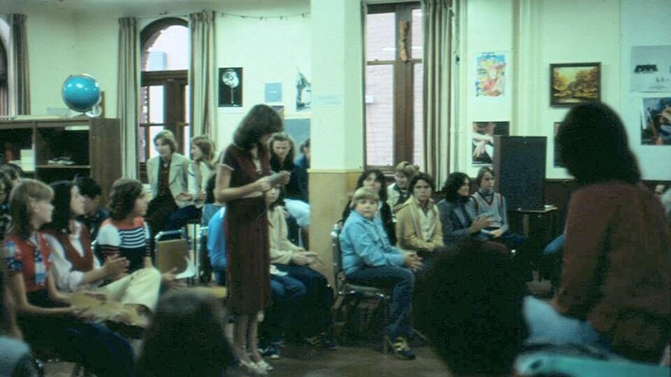 Des élèves sont rassemblés dans une classe.