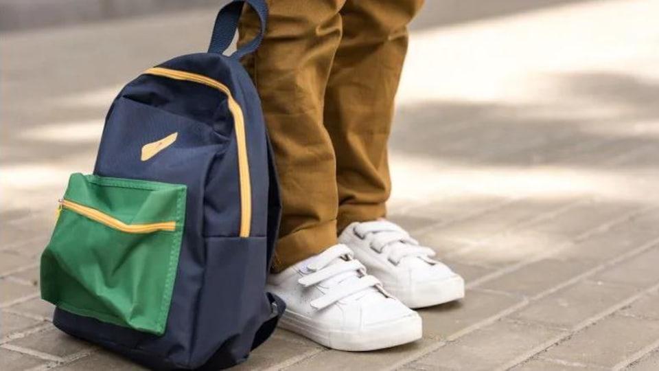 Un sac à dos bleu et vert se retrouve aux pieds d'une personne qui porte des souliers blancs et un pantalon beige.