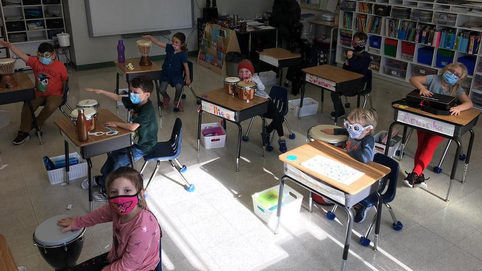 Des écoliers assis dans une classe qui jouent des instruments de percussion.