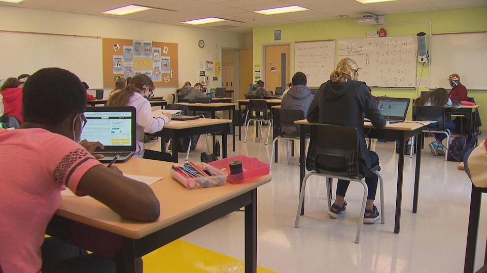 Des jeunes sont assis à leur pupitre et étudient.