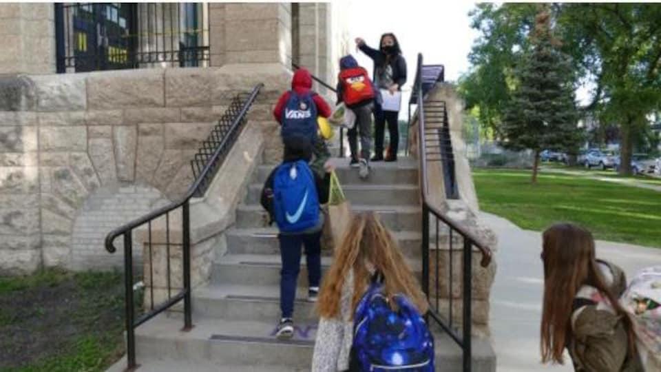 Des élèves munis de leur sac d'école montent des escaliers à l'extérieur d'une école.