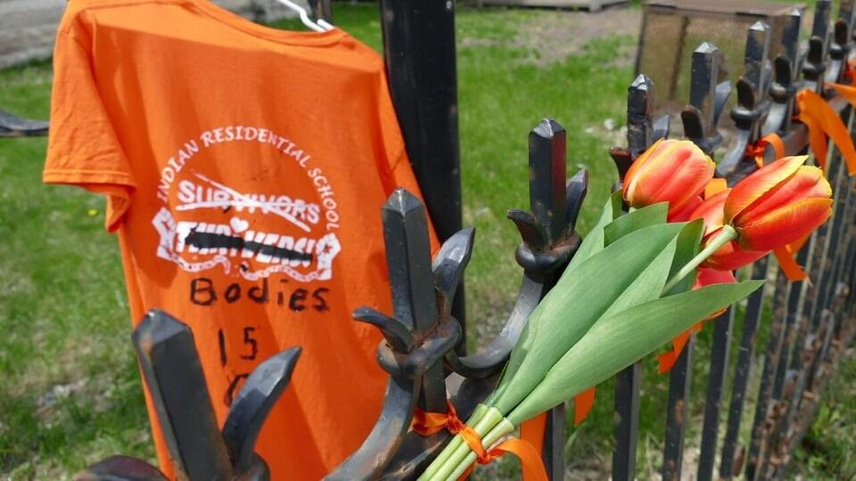 Un chandail orange est suspendu  à côté d'un bouquet de tulipes elles aussi orange.