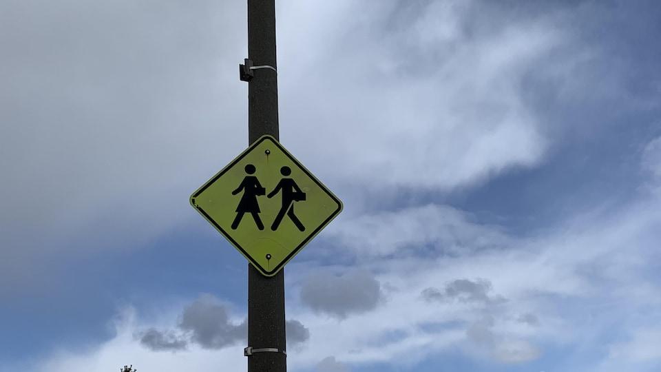Une pancarte avertissant les automobilistes à l'arrivée dans une zone scolaire.
