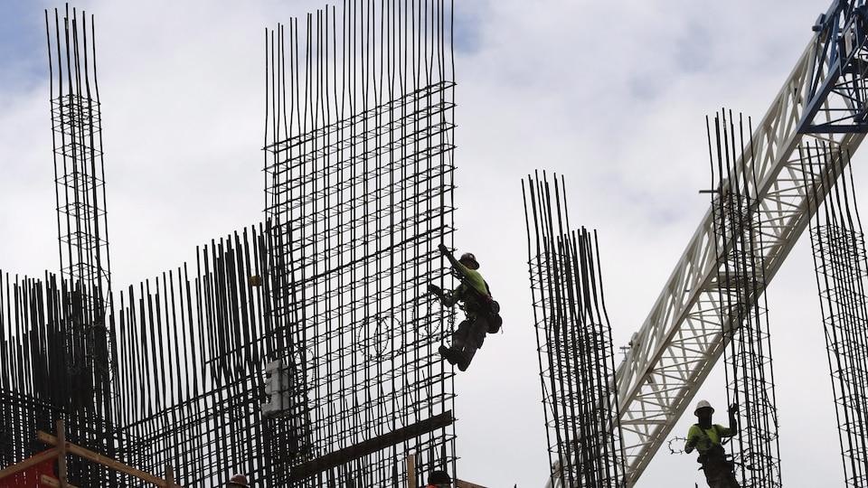 Des ouvriers s'affairent à la construction d'une tour d'habitation.