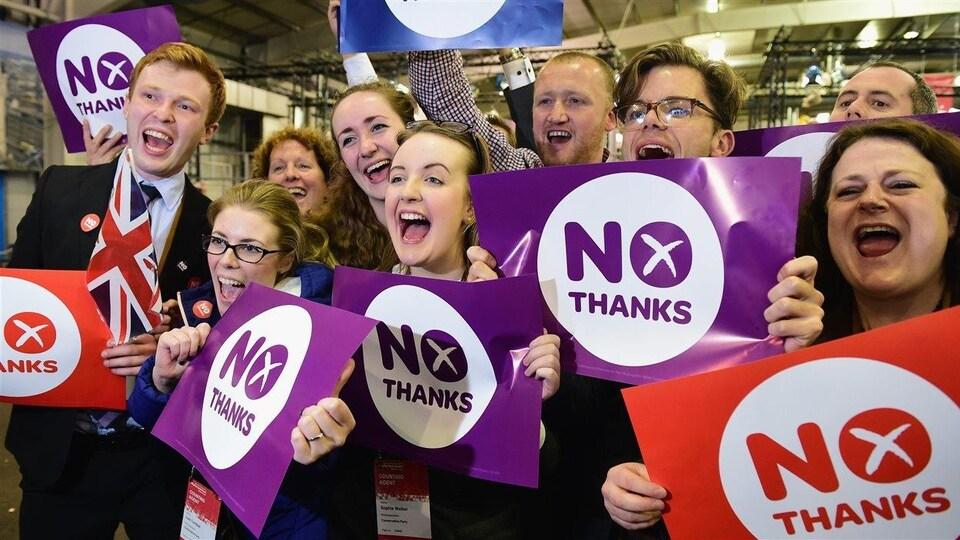 Des jeunes tiennent des pancartes sur lesquelles est écrit : «Non, merci».