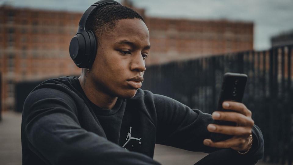 Un jeune homme, qui a un casque sur les oreilles et un téléphone dans les mains, écoute de la musique.