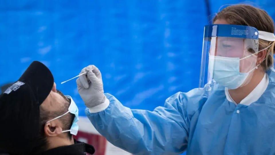 Un travailleur médical porte un masque chirurgical, un écran facial et des gants pendant qu'il effectue un test COVID-19 sur un homme non identifié à Montréal.