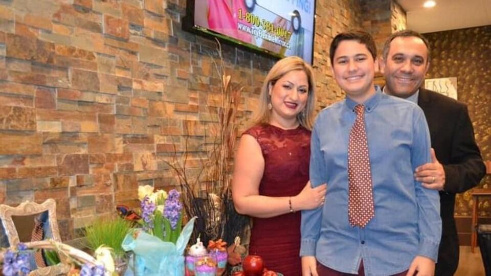 Un couple et leur adolescent, souriants lors d'une fête.