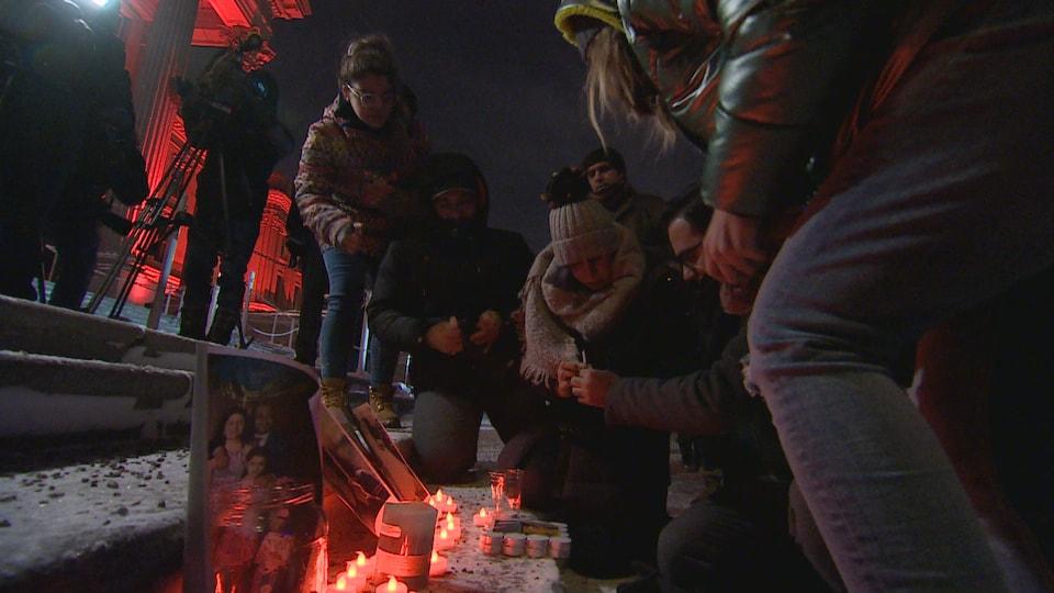 Des gens déposent des bougies et des photos des victimes de l'accident sur les marches de l'Assemblée législative.