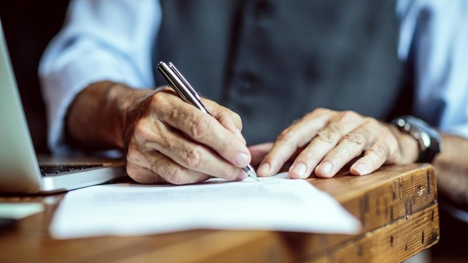Plan serré des mains d'un homme âgé signant un document.