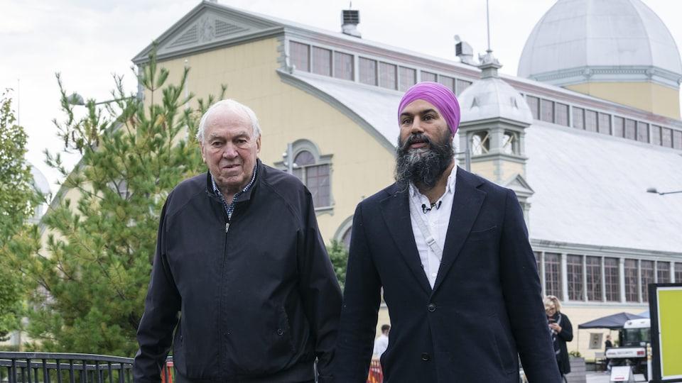 Ed Broadbent et Jagmeet Singh marchent côte à côte à l'extérieur.