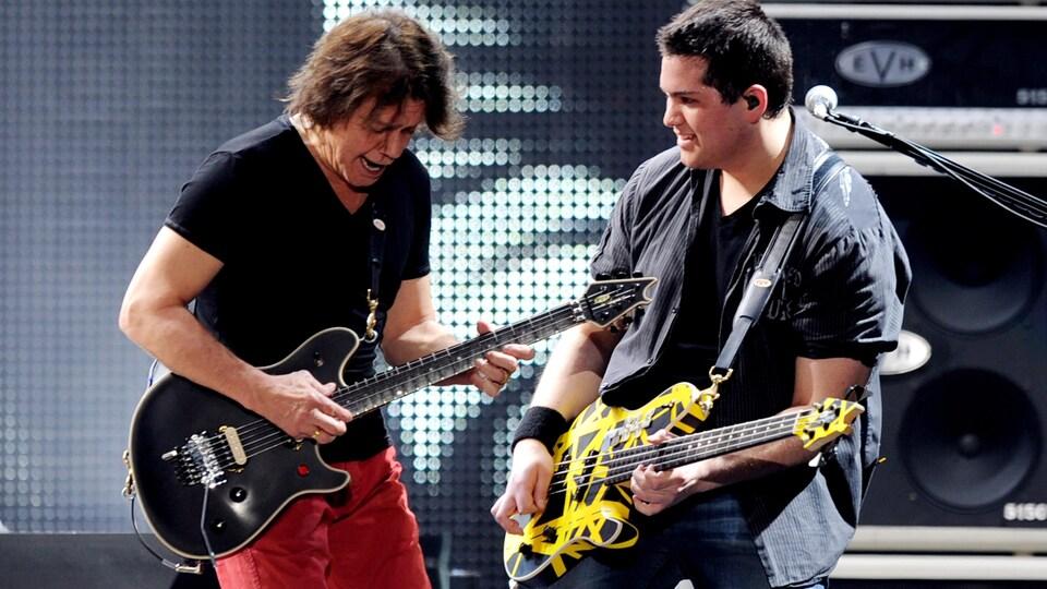 Les deux hommes jouent de la guitare sur scène.