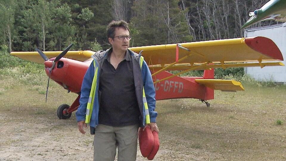 Eddy Métivier devant un petit avion.