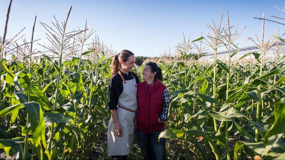 Une mère et sa fille se regardent dans les yeux au milieu d'un champ.