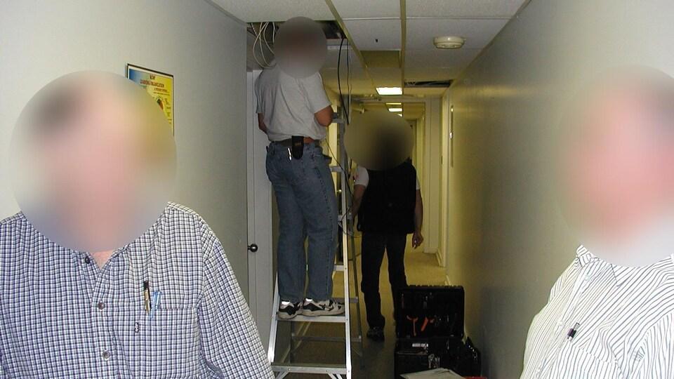 Des hommes en train d'installer des fils dans le plafond.