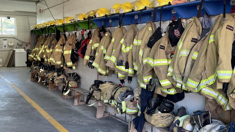 Un vestiaire dans lequel des habits de pompiers sont accrochés.