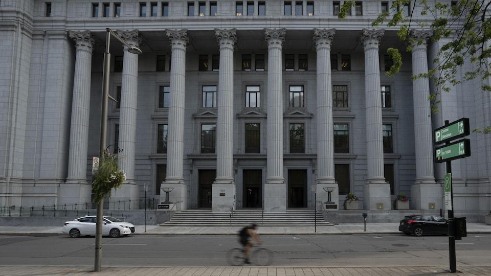 Un cycliste passe devant un édifice de style classique.